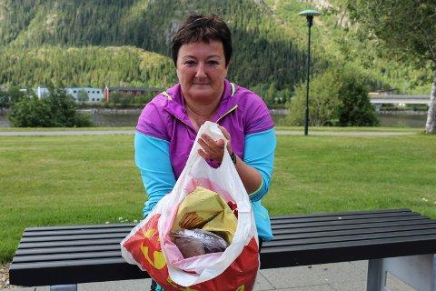 Anita Jensen viser fram en bærepose med søppel hun har plukket i nærheten av elveparken.