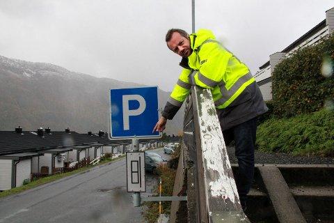PARKERING: Parkeringsskiltet er nylig montert av Vefsn kommune, og sier at det er lov å parkere i denne delen av Tjeldstia. Christer Amundsen peker på underskiltet, som viser at kun på langs- parkering er lov. Flere biler i bakgrunnen står på skrå. Det er ikke lov.