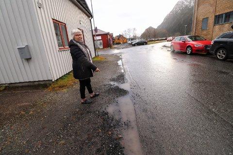 HULL OG SPRUTING: Bodhild Pedersen bor i huset t.v.  Hun er frustrert over at folk kjører over fortauet for å kunne passere møtende trafikk. - Fortauet blir fort hullete og fullt av vanndammer. Stein og sand sprutes på husveggen min. Siste året har mange parkert på motsatt side av gata. Da blir gata smalere, påpeker Pedersen.
