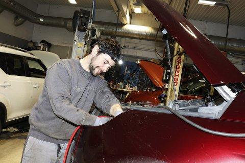 Mekanikeren: Emmit Martin er mekaniker ved Bilfokus AS i Mosjøen. Fredag feiret bedriften 10 år – med kaffe og kaker til kundene på dagtid, og festmiddag for de ansatte om kvelden. De profilerer seg som byens eneste lokaleide bilforretning. Foto: Stine Skipnes
