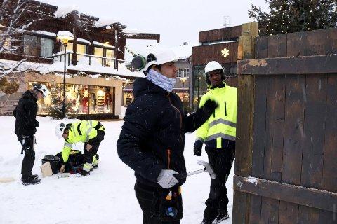 Snart jul: Hussein Alamiar og Yakob Ganamo er elever på Vg1 Bygg og anlegg ved Mosjøen videregående skole. – Det er artig å snekre. Vi satte opp bodene til Tiendebytte også, men nå er det vind og snø og vi må holde varmen, sier guttene fikser salgsboder til Julebyen Mosjøen. Foto: Stine Skipnes