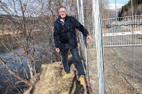 ATKOMST: Bjørn Brodtkorb står her ved det nyoppsatte viltgjerdet, ved Rossvoll sør for Skog i Mosjøen. Han vil at fiskere skal ha gode atkomstmuligheter til elva i form av flere overganger og underganger i forbindelse med jernbanesporet. Inntil den kommunale saksbehandlingen kommer på sporet igjen har Fylkesmannen satt en foreløpig stopper for bygging av gjerde videre sørover fra Kvalfors stasjon. Vefsna t.v., jernbanen t.h..