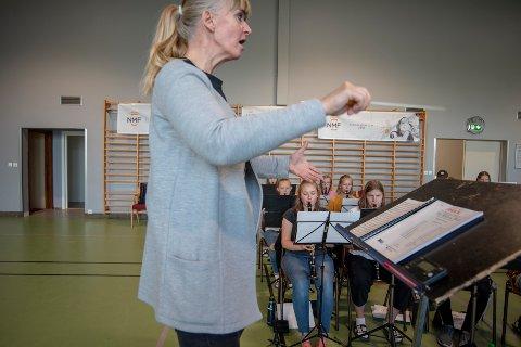 Dirigent Irene Anda fører ungdommene som deltar på sommermusikkskolen på Toppen Folkehøgskole gjennom verket «How to tame your dragon».