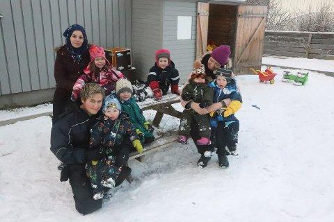 FORNØYDE: Her er noen av de ansatte og noen av ungene i Karius og Baktus kulturbarnehage på Trofors. De koste seg ute i nysnøen på tirsdag.
