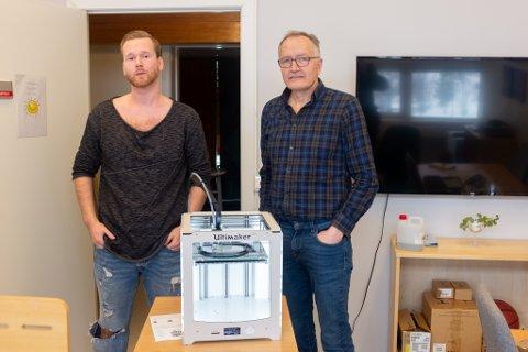 IKT-ansvarlig Bjørn-Tore Lund og rektor Kurt Henriksen foran en 3D-printer på Mosjøen videregående skole. Nå bidrar skolen med å produsere smittevernutstyr.