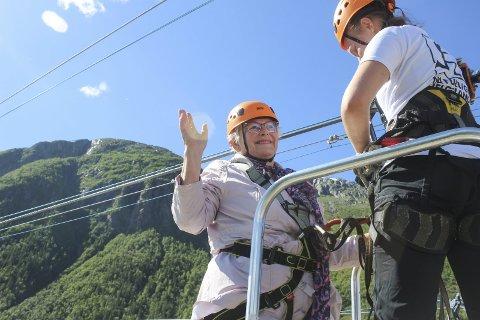 STRÅLENDE FORNØYD: Snart 88 år gamle Gerd Winther Solhaug er en tøffing. Hun tok zipline og var strålende fornøyd. Her får hun hjelp av Amalie Kummernes med utstyret. Foto: Per Vikan