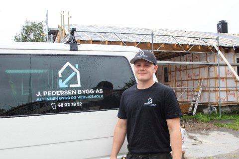 Joakim Pedersen har startet opp J. Pedersen Bygg AS. Her foran bilen sin og et hus han jobber med å renovere.