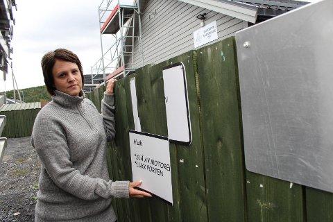 Ødelagt: Styrer Caroline Øyås Pedersen holder opp den delen av skiltet som har blitt ødelagt.  - En dag lå den biten på kontoret mitt da jeg kom, sier hun.