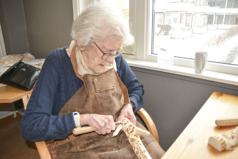 HÅNDARBEID: Astrid Olderskog (98) er fortsatt aktiv med treskjæring på Aktivitetssenteret for seniorer i Vefsn kommune. Hun er også en habil trekkspiller, men sier selv at hun for det meste spiller for «katto».  Foto: Ståle Elstad