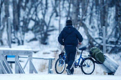 KIRKENES  20151116. Et par med barn passerer den norsk-russiske grensen på Storskog i Finnmark. De tre var blant et tyvetalls asylsøkere som krysset grensen tirsdag formiddag. Foto: Cornelius Poppe / NTB scanpix / TT / kod  20520