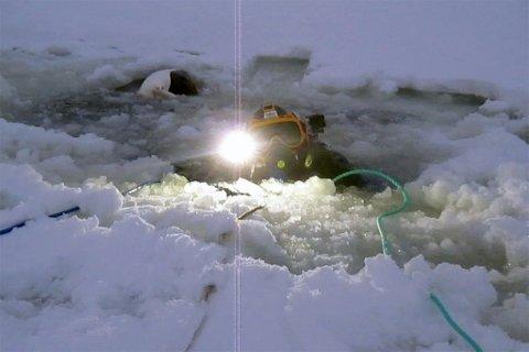 DUKKERT: Her kommer dykker opp av vannet etter å ha lokalisert snøscooteren i bunnen av vannet.