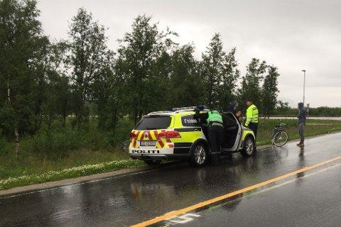 Mannen som slo til iFinnmarks fotograf ble lagt i jern på stedet og satt inn i politibilen av patruljen som ankom fra Karasjok. Mannen til høyre i bildet har ingenting med hendelsene å gjøre. (Foto: iFinnmark)