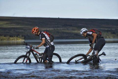 Syklister vader over et vann under terrengrittet OffroadFinnmark. Foto: Venche Jensen / OffroadFinnmark / NTB scanpix