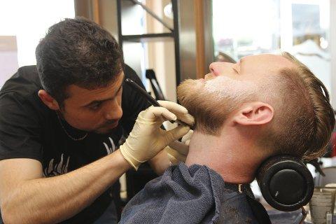I tiden: Barbering er blitt på moten. Abel Siro (29) både barberer og tatoverer på Frisørstua. Her er det skjegget til John Lupton som får seg en stuss.alle foto: Henriette Baumann sand