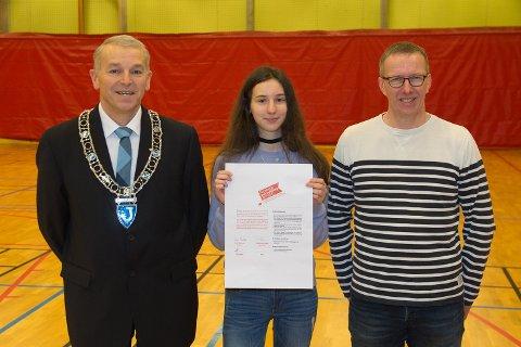 Ordfører Geir Knutsen (AP) sammen med elevrådsleder Aista Jucinskaite (15) og Børre Børresen ved Båtsfjord skole. Plakaten er lagd av en elev ved Båtsfjord skole, og skal henges opp rundt om i kommunen.