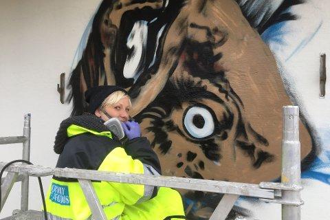 ZINA: Grafittikunstneren Linda Aslaksen, med kunstnernavnet Zina, skaper fiskekunst på veggen til fiskebruket på Sørvær.