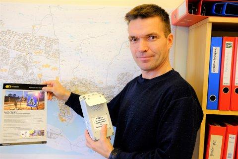 LYDFYR: Tony Kolstrøm viser fram lydfyrboksen som skal monteres der gangveien krysser Finnmarksveien og en SeeMe-plakat.