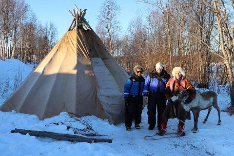 Utenfor lavvoen på Camp Alta står de to turistene og Gaup med reinen.