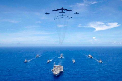 MASSIV BØLGE: USA har i løpet av få dager sendt bølge etter bølge med B-52 strategiske bombefly mot Russlands nærområder i ulike deler av verden. Dette bildet viser et amerikansk B-52 (i midten) som sammen med F/A-18 Hornets fra US Navy flyr over en amerikansk hangarskipgruppe anført av hangarskipet USS Ronald Reagan (CVN 76) 31. august 2018.