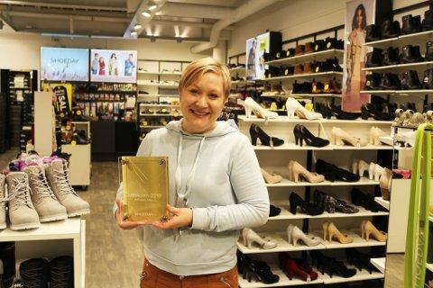 STOLT OG GLAD: Butikkleder Aase Elise Geithung er strålende fornøyd med prisen og gir æren til godt arbeidsmiljø.