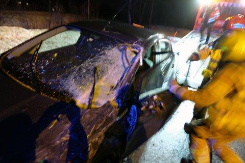 KNUST RUTE: Frontruta på personbilen ble knust. Her forsøker brannvesenet å skyva døra på plass.