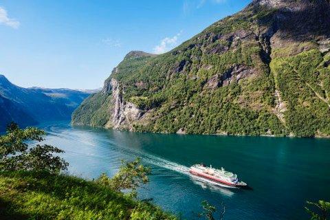 HÅPER PÅ JUNI-START: Hurtigruten håper å gradvis starte seilinger igjen fra juni. Her er MS Nordlys i sommervakre Geirangerfjorden. Foto: AGURTXANE CONCELLON/Hurtigruten