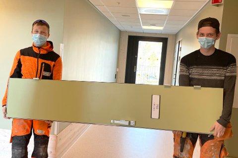 Oppe på Alta Omsorgssenter tar PEAB Bjørn Bygg seg av jobben med å ta av og på dørene. Her er lærlingene Kristian Rasmussen og Niklas Hoel Johansen i aksjon.