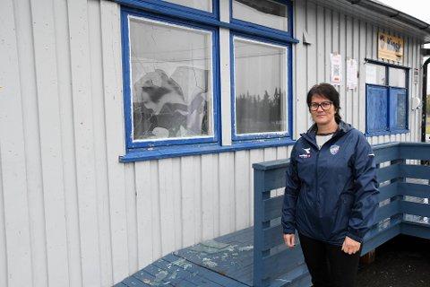 OPPGITT: Anne-Grethe Lillemoen er oppgitt etter nok et hærverk på Alta IFs bygg på Alta Idrettspark på Aronnes. Her står hun foran et knust vindu i kafébygget.