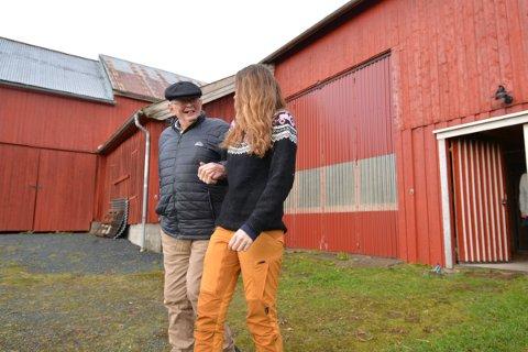 STØDIG HÅND: Demenssyke Ola Vatn setter pris på å ha den stødige hånda til Ida Stene Tangstad å holde i når han skal bevege seg fra fjøset og inn til hovedhuset på Maurtuva Vekstgård. – Det kan bli folkesnakk av dette,  spøker han til fotografen.