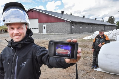 Knut-Inge Krogstad Hvesser viser fram apparatet som avdekker temperaturen i vegger og tak på bygninger. Gårdbruker Jørn Østreng på Hemnes har fått en full gjennomgang av gården.