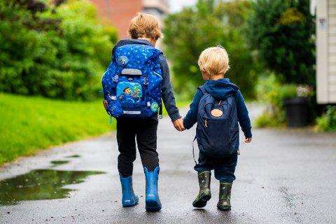 To barn er på vei til skole og barnehage med hver sin sekk på ryggen.