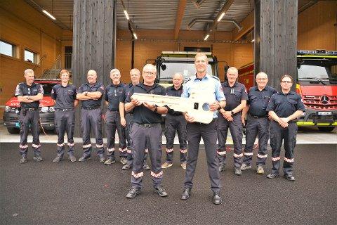 ENDELIG HERRE I EGET HUS: Endelig har mannskapene i Løken brannvesen fått sin storstue, en splitter ny brannstasjon til 20 millioner kroner. Her overleverer leder av Nedre Romerike brann- og redningsvesen, Arne Stadheim, en symbolsk kjempenøkkel i tre, det samme materialet om brannstasjonen er bygget i, til stasjonsleder Torleif Sønsterud. (De to i forgrunnen) Foto: Øivind Eriksen