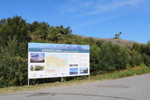 """Her er det nye """"byskiltet"""" plassert ved veien inn til Sandnessjøen. I bakgrunnen kan du se elgen."""