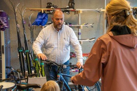 LÅNER UT: Lars Lauritzen er leder for BUA i Alstahaug. Her viser han fram en sykkel til en nysgjerrig familie som ønsker å låne utstyr.
