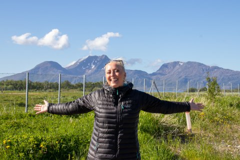 STRÅLER: Journalist, programleder, Stjernekamp-dommer og nå friluftsmenneske Mona B. Riise smilte i kapp med sola etter fem dager på Helgelandskysten. Her er hun avbildet med Dønnamannen i bakgrunnen fra flyplassen på Stokka.