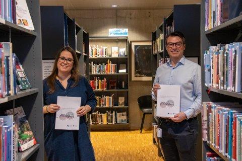 ØNSKER INNSPILL: Kulturkonsulent Johanne Markvoll og kultursjef Odd Arnold Skogsholm holder opp forprosjektet til historisk verk om Alstahaug. Om økonomien går i orden, er håpet at man kan finne verket mellom disse bokhyllene i Kulturbadets bibliotek.