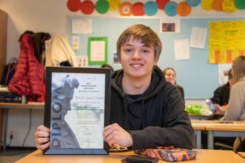 BEVISET: Frederik Egelund Edvardsen holder opp det synlige beviset på at han ble nummer 28 i finalen i Nils Henrik Abels matematikkonkurranse, bedre kjent som Abelkonkurransen.