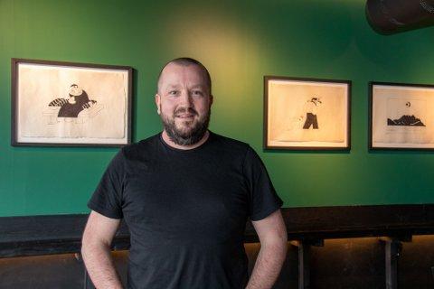 GLADLAKS: Ivar Sørra er daglig leder for sushi-restauranten Kontoret i Sandnessjøen. I bakgrunnen henger japansk-inspirert kunst med lokale motiver, spesialdesignet for utestedet.