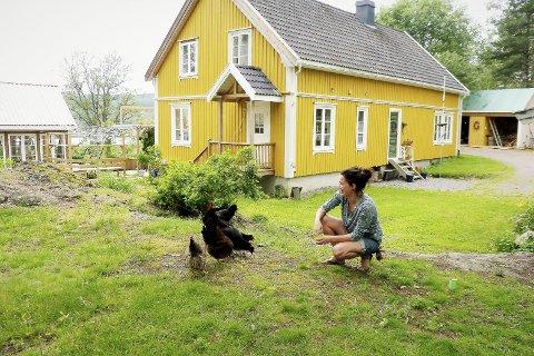 Det klukker på tunet: Ingvild Stomsvik og hønene i det grønne. Her er det viktig at alle skal trives, og at hagen skal henge sammen med det som er inne. Foto: Vita Elise Thorup Eliassen