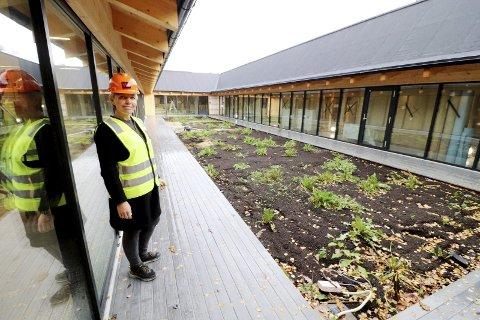 Hjertet i det nye bygget: – Selve rosinen i pølsa, viser daglig leder Annett Henriksen om atriet mellom barnehagedelen og skoledelen av nybygget. Foto: Pål Nordby