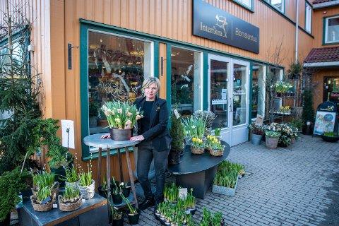 SELVBETJENING: Marianne Trondsen, innehaver av Blomsterstua på Jessheim, setter blomster og løker utenfor og ber kunder som ikke vil inn i butikken om å forsyne seg selv.