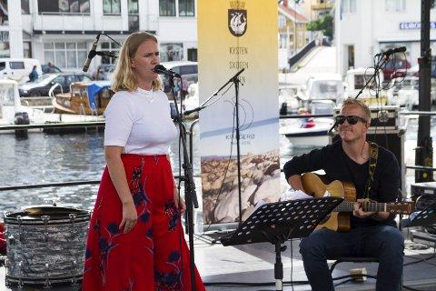 Sang: Det kan ikke bli annet enn idyllfølelse når lokale artister spiller opp, mens båter tokker inn i Blindtarmen i bakgrunnen. Her med Oda Dahll som sanger og Knut Wærstad Mindrebø på gitar.