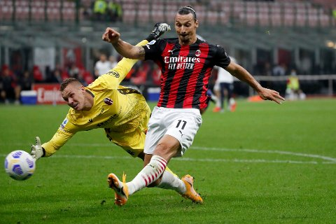 AC Milan's Zlatan Ibrahimovic, right, kick the ball as Bologna's goalkeeper Lukasz Skorupski try to stop the ball during the Serie A soccer match between AC Milan and Bologna at the San Siro stadium, in Milan, Italy, Monday, Sept. 21, 2020. (AP Photo/Antonio Calanni)