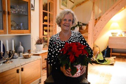 Else Helleland i Dimmelsvik får første juleblomen av Kvinnheringen i år.