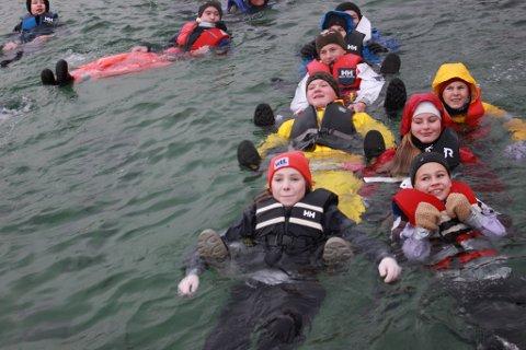 34 elevar og to lærarar ved Øyatun skule på Halsnøy hoppa i sjøen og tok eit vinterbad. Her ser du nokre av dei plaska i det iskalde vatnet.