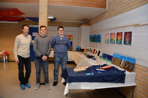 Lærar Kjell Rune Asmervik (t.v.) er imponert over utstillinga elevane Erik Voster Solberg, Lars Erik Skåtun (t.h.) og dei andre elevane ved 10. trinn på Husnes ungdomsskule har laga.