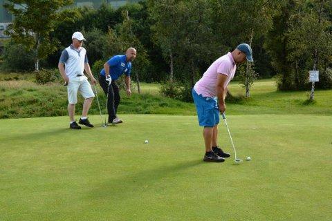 Verner Fjelland (rosa trøye) puttar seg inn til ein andreplass i klubbmeisterskapet til Kvinnherad Golfklubb. Henning Sæbø (t.v.) og Jan Gunnar Koløy følgjer nøye med.