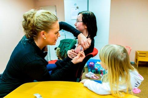 Dotter til Ida er med på helsestasjonen. Ho studerer nøye medan helse-søster Line Holmedal stikk nåla inn i skuldra til mora.