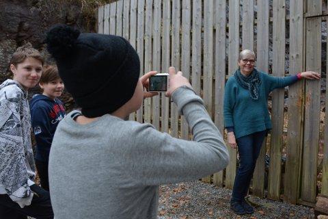 Andreas tar bilde til avisa av rektor Lila Moberg ved gjerdet bak skulen. Vetle og Sander følgjer spente med.