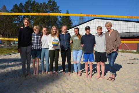 Desse ungdomane er blant dei ivrige sandvolleyballspelarane til Strand-Ulv. Frå venstre: Lars Kristian Ekeland (13), Sigve Rødland (15), Tuva Berge (15), Ina Traavik (15), Hanna Eikeland (15), Tora Aksnes (16), Sturla Gaugstad (14) og Henrik Tholo Aasen (14), samt trenar og tidlegare proffspelar Ragni Hestad. I bakgrunnen kjem den nye innandørs sandvolleyballhallen.